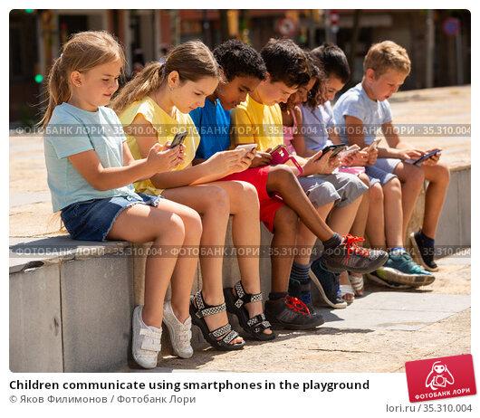 Children communicate using smartphones in the playground. Стоковое фото, фотограф Яков Филимонов / Фотобанк Лори
