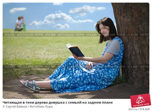 Читающая в тени дерева девушка с семьей на заднем плане, фото № 314420, снято 24 июня 2007 г. (c) Сергей Байков / Фотобанк Лори