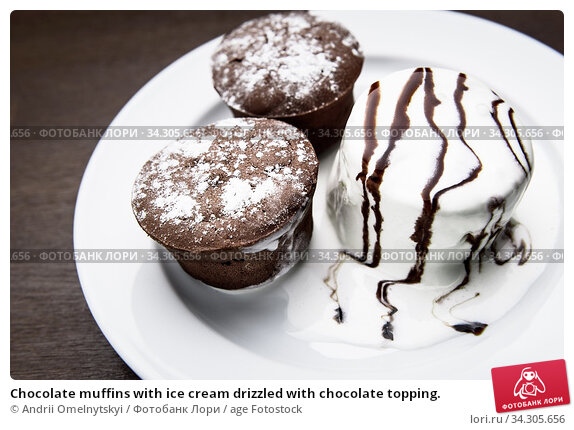 Chocolate muffins with ice cream drizzled with chocolate topping. Стоковое фото, фотограф Andrii Omelnytskyi / age Fotostock / Фотобанк Лори