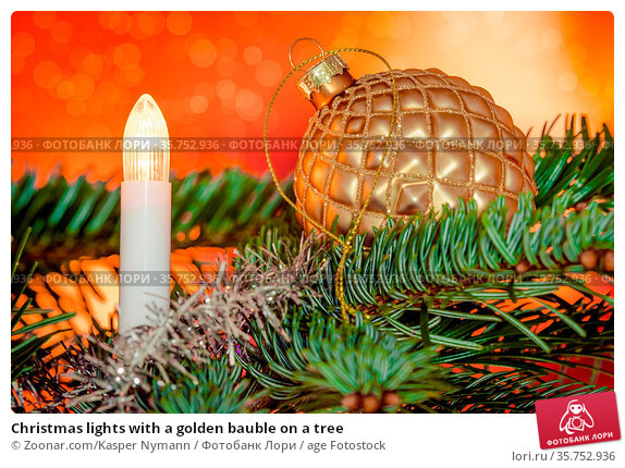 Christmas lights with a golden bauble on a tree. Стоковое фото, фотограф Zoonar.com/Kasper Nymann / age Fotostock / Фотобанк Лори