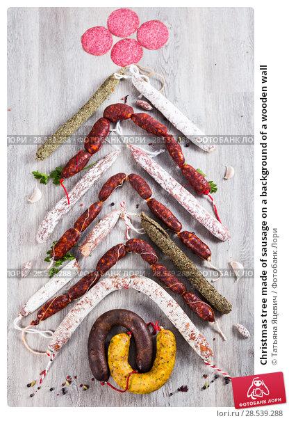 Купить «Christmas tree made of sausage on a background of a wooden wall», фото № 28539288, снято 17 ноября 2016 г. (c) Татьяна Яцевич / Фотобанк Лори