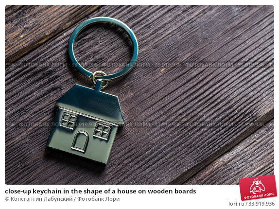 close-up keychain in the shape of a house on wooden boards. Стоковое фото, фотограф Константин Лабунский / Фотобанк Лори