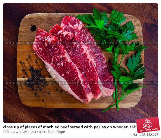 close up of pieces of marbled beef served with parley on wooden table. Стоковое фото, фотограф Яков Филимонов / Фотобанк Лори