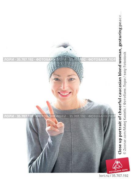 Close up portrait of cheerful caucasian blond woman, gesturing peace... Стоковое фото, фотограф Zoonar.com/Matej Kastelic / easy Fotostock / Фотобанк Лори