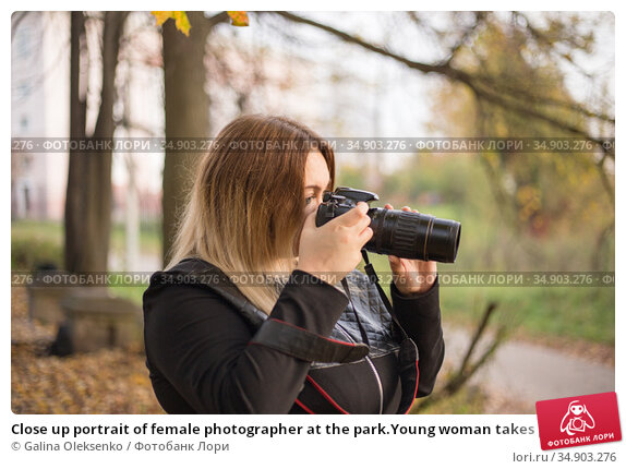 Close up portrait of female photographer at the park.Young woman takes picture in an autumn park. Стоковое фото, фотограф Galina Oleksenko / Фотобанк Лори