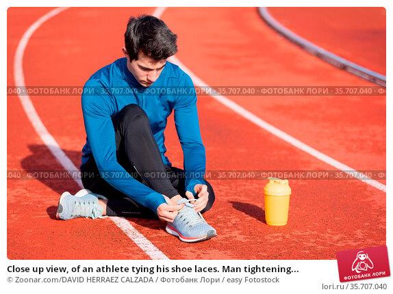 Close up view, of an athlete tying his shoe laces. Man tightening... Стоковое фото, фотограф Zoonar.com/DAVID HERRAEZ CALZADA / easy Fotostock / Фотобанк Лори