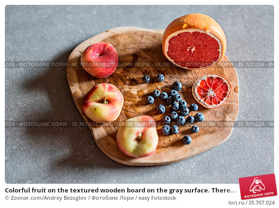 Colorful fruit on the textured wooden board on the gray surface. There... Стоковое фото, фотограф Zoonar.com/Andrey Bezuglov / easy Fotostock / Фотобанк Лори