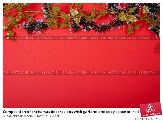 Composition of christmas decorations with garland and copy space on red background. Стоковое фото, агентство Wavebreak Media / Фотобанк Лори