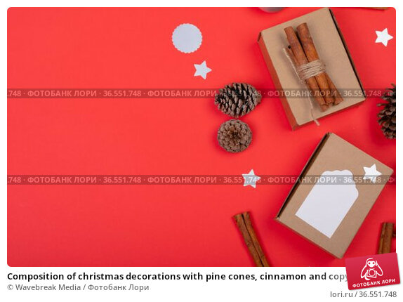 Composition of christmas decorations with pine cones, cinnamon and copy space on red background. Стоковое фото, агентство Wavebreak Media / Фотобанк Лори