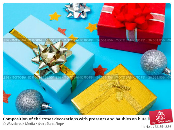 Composition of christmas decorations with presents and baubles on blue background. Стоковое фото, агентство Wavebreak Media / Фотобанк Лори
