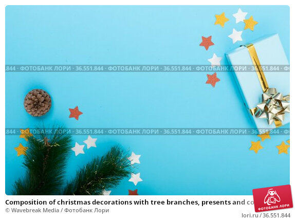 Composition of christmas decorations with tree branches, presents and copy space on blue background. Стоковое фото, агентство Wavebreak Media / Фотобанк Лори