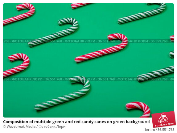 Composition of multiple green and red candy canes on green background. Стоковое фото, агентство Wavebreak Media / Фотобанк Лори
