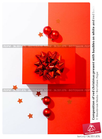 Composition of red christmas present with baubles on white and red background. Стоковое фото, агентство Wavebreak Media / Фотобанк Лори