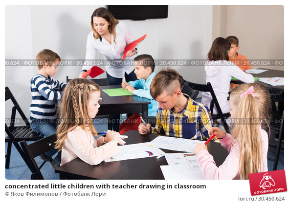 concentrated little children with teacher drawing in classroom. Стоковое фото, фотограф Яков Филимонов / Фотобанк Лори