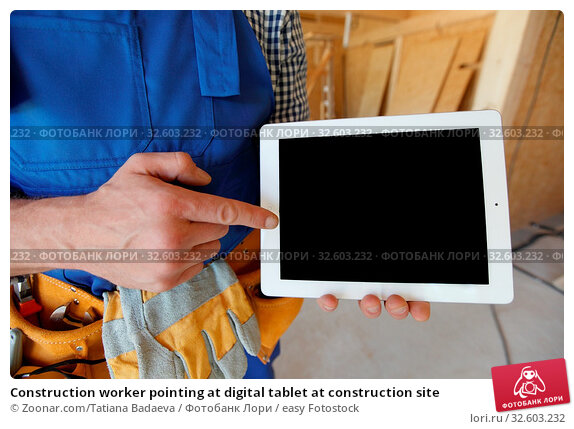 Construction worker pointing at digital tablet at construction site. Стоковое фото, фотограф Zoonar.com/Tatiana Badaeva / easy Fotostock / Фотобанк Лори