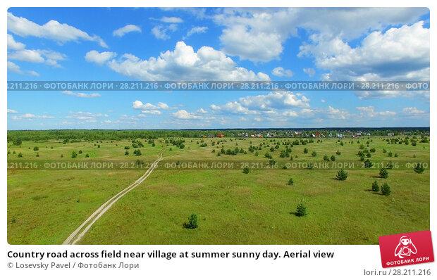 Купить «Country road across field near village at summer sunny day. Aerial view», фото № 28211216, снято 25 апреля 2019 г. (c) Losevsky Pavel / Фотобанк Лори