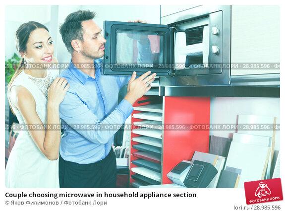 Купить «Couple choosing microwave in household appliance section», фото № 28985596, снято 15 июня 2017 г. (c) Яков Филимонов / Фотобанк Лори