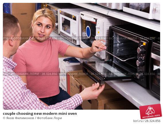 Купить «couple choosing new modern mini oven», фото № 28324856, снято 1 марта 2018 г. (c) Яков Филимонов / Фотобанк Лори