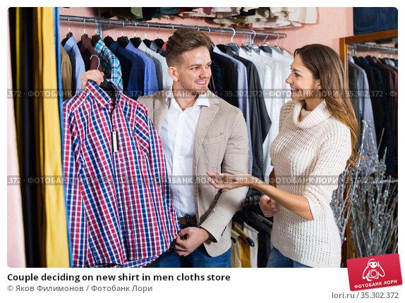 Couple deciding on new shirt in men cloths store. Стоковое фото, фотограф Яков Филимонов / Фотобанк Лори