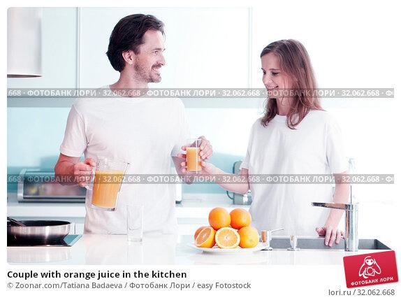Couple with orange juice in the kitchen. Стоковое фото, фотограф Zoonar.com/Tatiana Badaeva / easy Fotostock / Фотобанк Лори