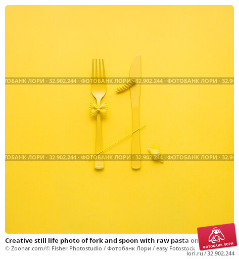 Creative still life photo of fork and spoon with raw pasta on yellow background. Стоковое фото, фотограф Zoonar.com/© Fisher Photostudio / easy Fotostock / Фотобанк Лори