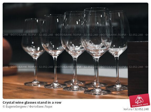 Crystal wine glasses stand in a row. Стоковое фото, фотограф EugeneSergeev / Фотобанк Лори
