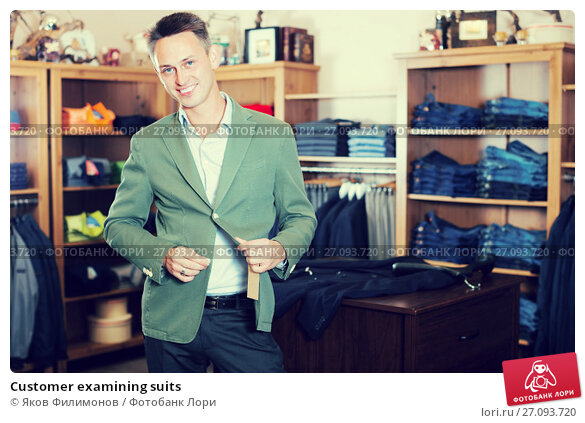 Купить «Customer examining suits», фото № 27093720, снято 28 марта 2017 г. (c) Яков Филимонов / Фотобанк Лори