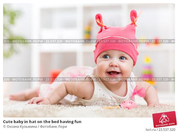 Купить «Cute baby in hat on the bed having fun», фото № 23537320, снято 7 октября 2015 г. (c) Оксана Кузьмина / Фотобанк Лори
