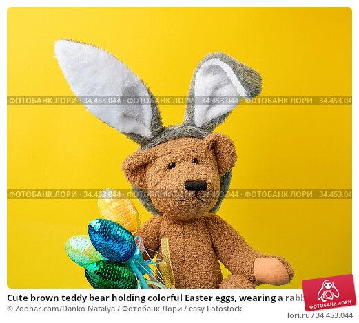Cute brown teddy bear holding colorful Easter eggs, wearing a rabbit... Стоковое фото, фотограф Zoonar.com/Danko Natalya / easy Fotostock / Фотобанк Лори