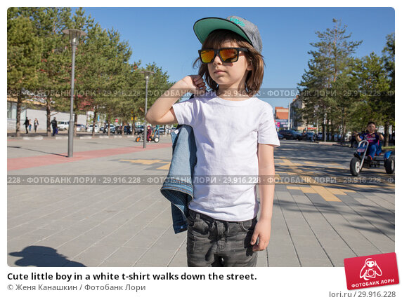 Купить «Cute little boy in a white t-shirt walks down the street.», фото № 29916228, снято 23 мая 2018 г. (c) Женя Канашкин / Фотобанк Лори