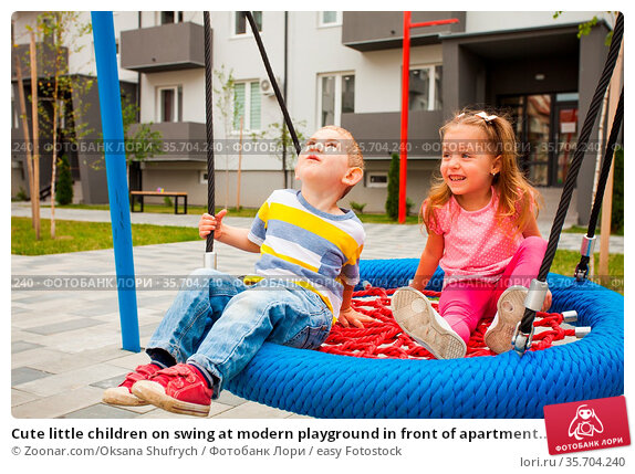 Cute little children on swing at modern playground in front of apartment... Стоковое фото, фотограф Zoonar.com/Oksana Shufrych / easy Fotostock / Фотобанк Лори