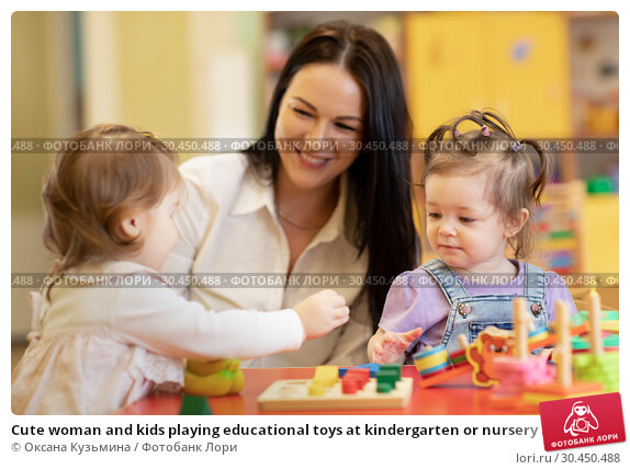 Cute woman and kids playing educational toys at kindergarten or nursery room. Стоковое фото, фотограф Оксана Кузьмина / Фотобанк Лори