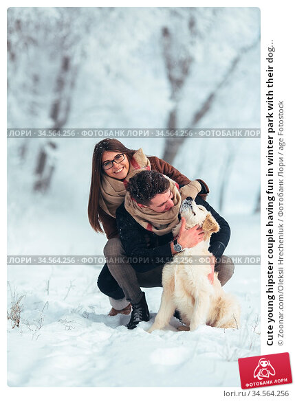 Cute young hipster couple having fun in winter park with their dog... Стоковое фото, фотограф Zoonar.com/Oleksii Hrecheniuk / age Fotostock / Фотобанк Лори