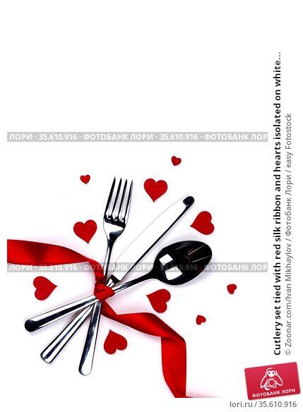 Cutlery set tied with red silk ribbon and hearts isolated on white... Стоковое фото, фотограф Zoonar.com/Ivan Mikhaylov / easy Fotostock / Фотобанк Лори