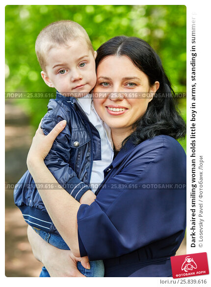 Купить «Dark-haired smiling woman holds little boy in arms, standing in summer park», фото № 25839616, снято 22 мая 2016 г. (c) Losevsky Pavel / Фотобанк Лори