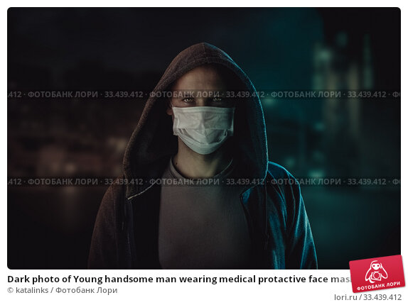 Купить «Dark photo of Young handsome man wearing medical protactive face mask in night street», фото № 33439412, снято 25 марта 2020 г. (c) katalinks / Фотобанк Лори