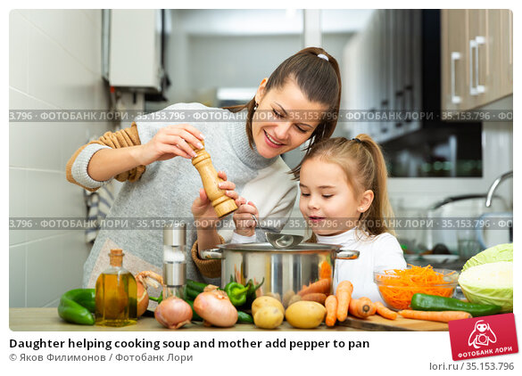 Daughter helping cooking soup and mother add pepper to pan. Стоковое фото, фотограф Яков Филимонов / Фотобанк Лори