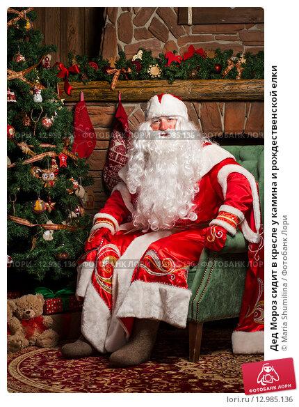 Дед Мороз сидит в кресле у камина и рождественской елки, фото № 12985136, снято 15 октября 2015 г. (c) Maria Shumilina / Фотобанк Лори