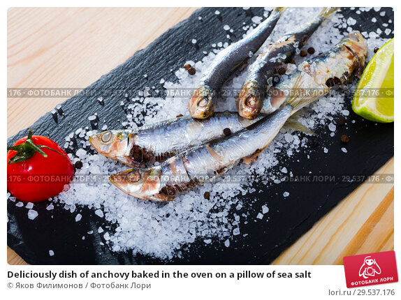 Deliciously dish of anchovy baked in the oven on a pillow of sea salt. Стоковое фото, фотограф Яков Филимонов / Фотобанк Лори