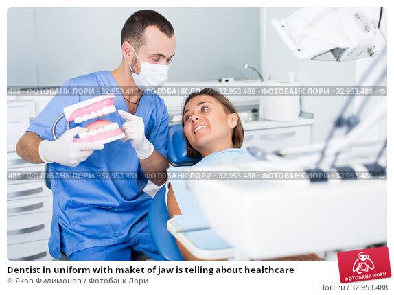 Dentist in uniform with maket of jaw is telling about healthcare. Стоковое фото, фотограф Яков Филимонов / Фотобанк Лори