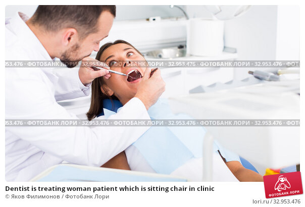Dentist is treating woman patient which is sitting chair in clinic. Стоковое фото, фотограф Яков Филимонов / Фотобанк Лори