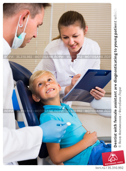 Dentist with female assistant are diagnosticating to young patient which is sitting. Стоковое фото, фотограф Яков Филимонов / Фотобанк Лори