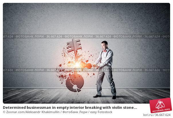 Determined businessman in empty interior breaking with violin stone... Стоковое фото, фотограф Zoonar.com/Aleksandr Khakimullin / easy Fotostock / Фотобанк Лори