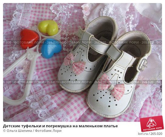 Детские туфельки и погремушка на маленьком платье, фото № 265020, снято 22 апреля 2008 г. (c) Ольга Шилина / Фотобанк Лори