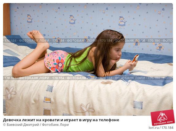 Девочка лежит на кровати и играет в игру на телефоне, фото № 170184, снято 6 января 2008 г. (c) Баевский Дмитрий / Фотобанк Лори