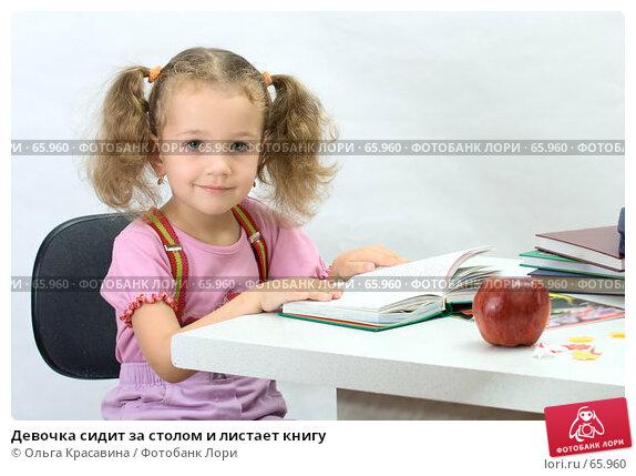 Девочка сидит за столом и листает книгу, фото № 65960, снято 28 июля 2007 г. (c) Ольга Красавина / Фотобанк Лори