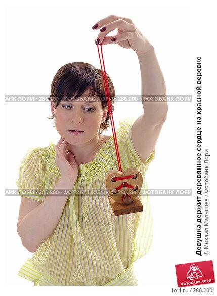 Девушка держит деревянное сердце на красной веревке, фото № 286200, снято 12 мая 2008 г. (c) Михаил Малышев / Фотобанк Лори