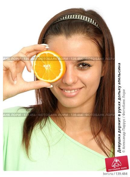 Девушка держит в руках дольку апельсина, фото № 139484, снято 5 сентября 2007 г. (c) Александр Паррус / Фотобанк Лори