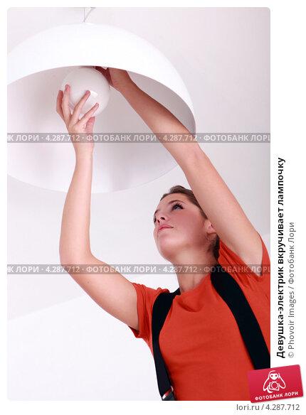 Купить «Девушка-электрик вкручивает лампочку», фото № 4287712, снято 3 ноября 2010 г. (c) Phovoir Images / Фотобанк Лори