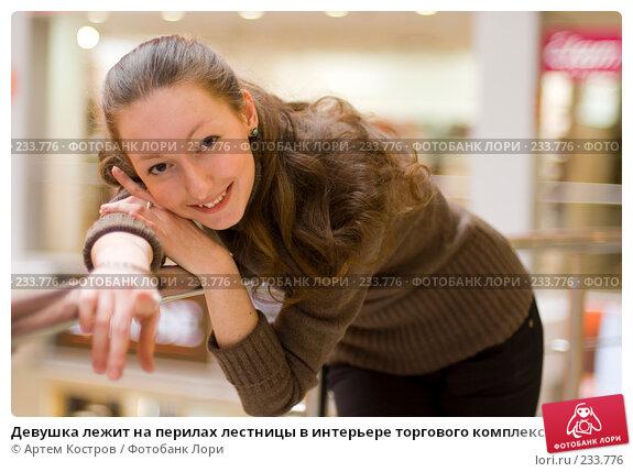 Девушка лежит на перилах лестницы в интерьере торгового комплекса и улыбается, фото № 233776, снято 5 марта 2008 г. (c) Артем Костров / Фотобанк Лори